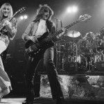 Alex Lifeson (left) and Geddy Lee (with Neil Peart on drums) on stage in 1976 on the tour that followed the release of 2112</em