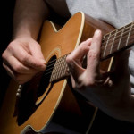 Closeup of guitar and muscian's hands.